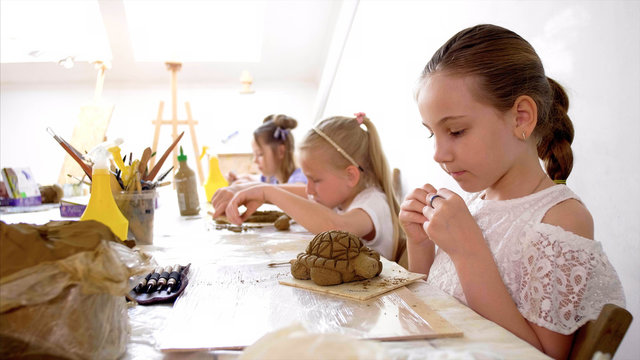 Children are sculpting toys from wet clay. They are using special tools under the guidance of a teacher on art lesson in workshop in elementary school.