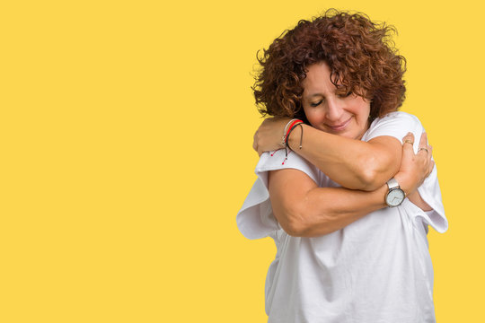 Beautiful middle ager senior woman wearing white t-shirt over isolated background Hugging oneself happy and positive, smiling confident. Self love and self care