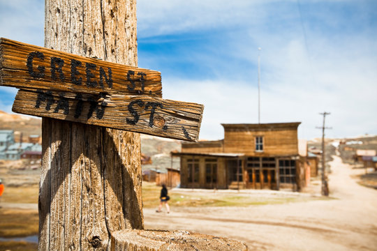 Old street signs at the main intersection in the Bodie ghost town in California. The old Wheaton & Hollis Hotel is in the background.