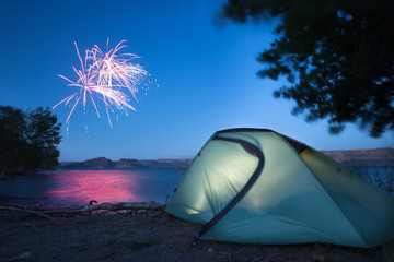 A tent glows my lamp light as nearby campers set of fireworks in celebration of the fourth of July at Banks Lake in central Washington.