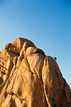 A man climbs Toe Jam 5.7 on the east face of the Old Woman Rock in the Hidden Valley Campground at Joshua Tree.
