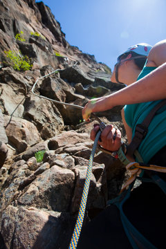 A woman belays a climber with an auto locking belay device.