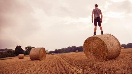 Fields, Ditzingen, Germany: Young man with backpack stands on bale of straw and overlooks the landscape while a thunderstorm is tearing in.