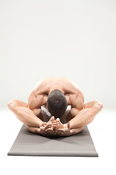 Young bodybuilder doing yoga on mat