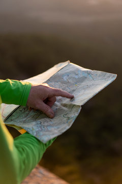 Close up of senior male hands holding a map on top of mountain during sunset