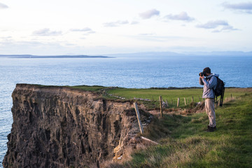 Photographer exploring the Cliffs of Moher at sunset