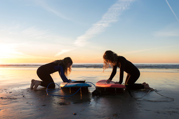 young girls waxing their surfboards at sunset