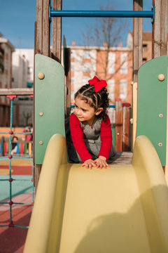 Little girl with curly hair is playing in a park