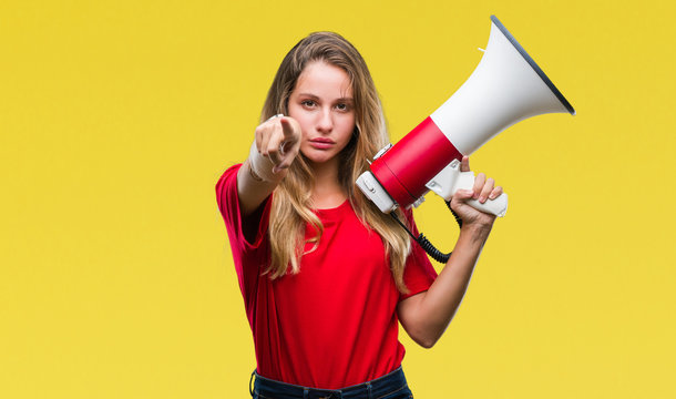 Young beautiful blonde woman yelling through megaphone over isolated background pointing with finger to the camera and to you, hand sign, positive and confident gesture from the front
