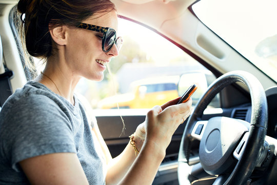 Woman using smart phone in car during summer