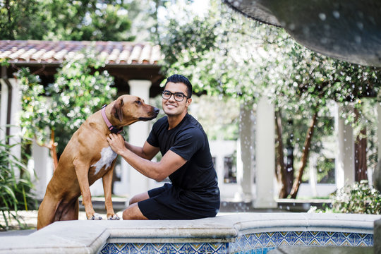 Young handsome man embracing his dog by Spanish Patio