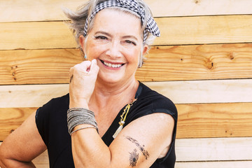 Rock and alternative cheerful senior caucasian woman show her tatoo on the arm smiilng at the camera - no limit age to have fun and enjoy lifestyle for old people - wooden background