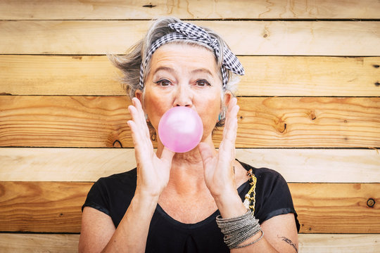 Funny and alternative old people caucasian beautiful woman with pink bubble chewing gum - portrait of youth active senior lady having fun - no limit age lifestyle concept