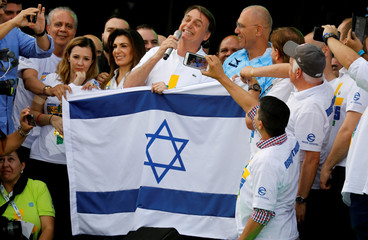 Brazil's President Jair Bolsonaro poses for picture with Israeli flag after an evangelical march to celebrate Corpus Christi in Sao Paulo