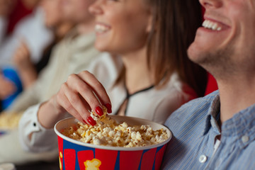 Selective focus of female hand taking delicious cheese popcorn in cinema. Cheerful pair watching new interesting comedy and eating tasty snack. Concept of relaxation and entertainment.