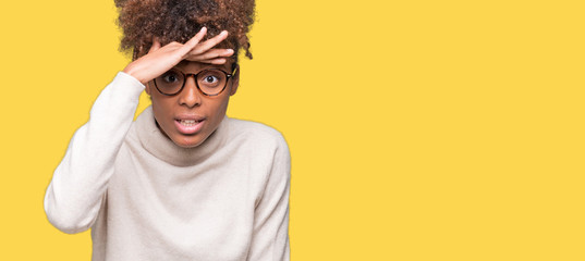 Beautiful young african american woman wearing glasses over isolated background very happy and smiling looking far away with hand over head. Searching concept. Fotoväggar