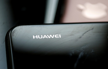Logo of Huawei is pictured as a worker refurbishes a cell phone at a workshop of the Oxflo company, specialised in refurbishment of broken European smartphones in Lusignac