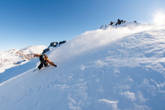 A women snowboards powder on a sunny bluebird day in Argentina.