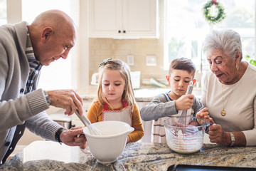 Multigenerational family cooking pancakes for breakfast