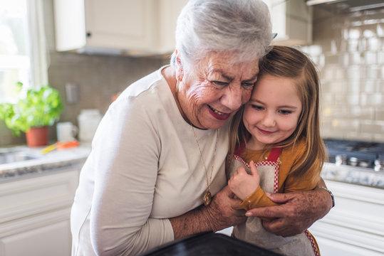 Close up of great grandmother hugging great granddaughter