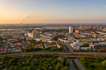 aerial view of the city of rostock, railway tracks, river warnow and power plant chimney in the background