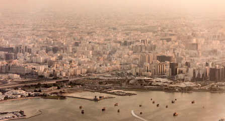 Aerial view of city of Doha, Qatar at sunset with dusty haze.