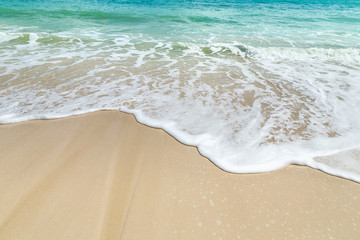 white soft wave rolling splash on empty tropical sandy beach in sunny day Wall mural