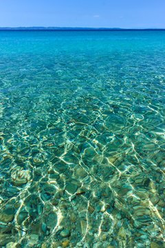 Close-up photo of clear, shallow sea water in Sithonia, Greece. Summer scenery