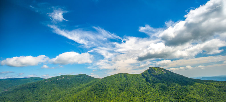 Panoramic photo of puffy clouds move over the mountains along the Blue Ridge Parkway in North Carolina, USA.