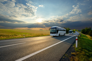 Fotobehang - Two white buses traveling on the asphalt road in rural landscape at sunset with dramatic clouds