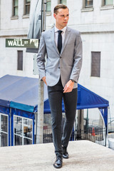 Young Businessman Street Fashion in New York City. Man wearing gray blazer, white undershirt, black tie, pants, leather shoes, standing on street outside office by Wall Street sign, looking forward..