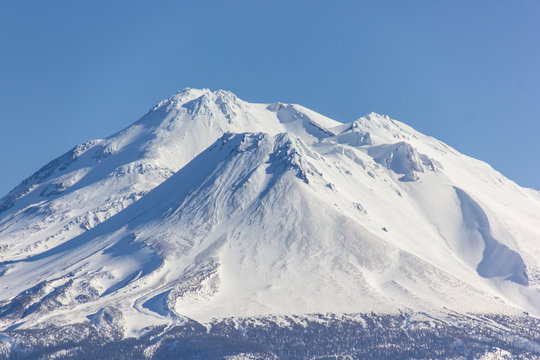 Mount Shasta covered in snow in a blue sky