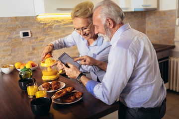 Aged couple busy look at digital tablet while having delicious breakfast at home kitchen