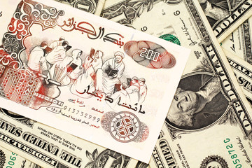 A macro image of a beige two hundred Algerian dinar bank note on a background of American one dollar bills