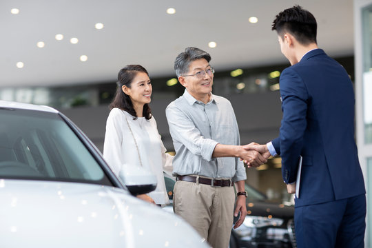 Happy mature couple choosing car in showroom