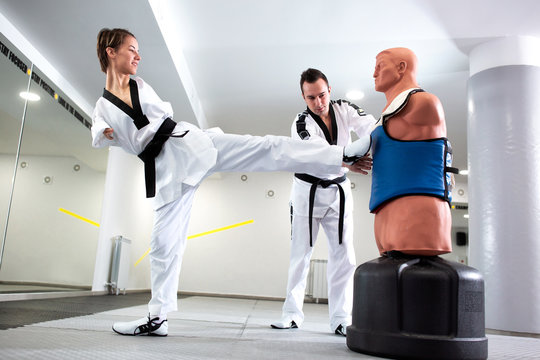 Experienced martial art coach teaching taekwondo to his student with physical disability