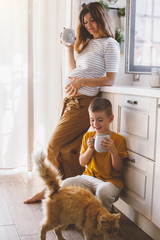 Pregnant mom with kid drinking tea together in the kitchen