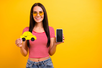 Portrait charming student lady weekend hold hand paper card taxi touch screen isolated leisure long haircut trendy eyeglasses eyewear yellow background denim jeans red striped stylish t-shirt she her Fototapete