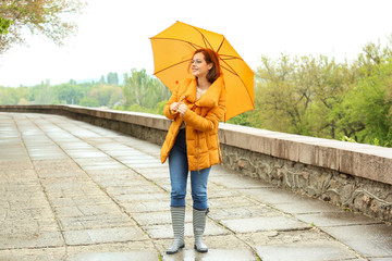 Beautiful young woman with umbrella outdoors on rainy day Fototapete