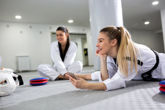Martial art girl doing some stretching and looking at her mobile phone