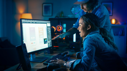 Two Friends or a Couple Discuss Mobile Design Interface on a Computer Screen. Pretty Black Girl Shows Her Work to a Young Man and He Shares Creative Ideas. Cozy Room is Lit with Warm and Neon Light.