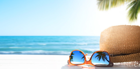 Sunny tropical beach vacation background; glasses and palm tree reflex Fototapete