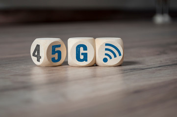 Cubes and dice with 4G and 5G on wooden background