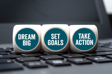 Cubes and dice with dream big, set goals and take action on laptop keyboard