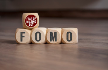 Cubes and dice with FOMO Fear of missing out on wooden background