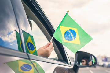 Woman or Girl Holding Flag of Brazil from the open car window. Concept Fototapete