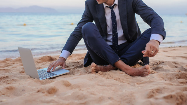 close up photo of a young man in suit with laptop working on the beach and talking to someone