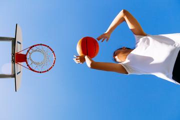 Young girl shooting basket outdoors