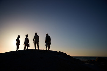 Silhouette Of Senior Friends Standing On Rocks By Sea On Vacation At Sunset Fototapete