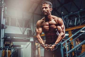 Body Building Workout at the Gym. Handsome Bodybuilder Working out in the gym, performing Cross over exercise for Chest Muscles